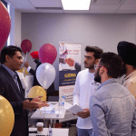Hanson College Brampton students speaking to a male presenter at a Career Fair