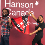 African American male and female staff members of Hanson College Brampton holding Toronto Raptors flag and smiling