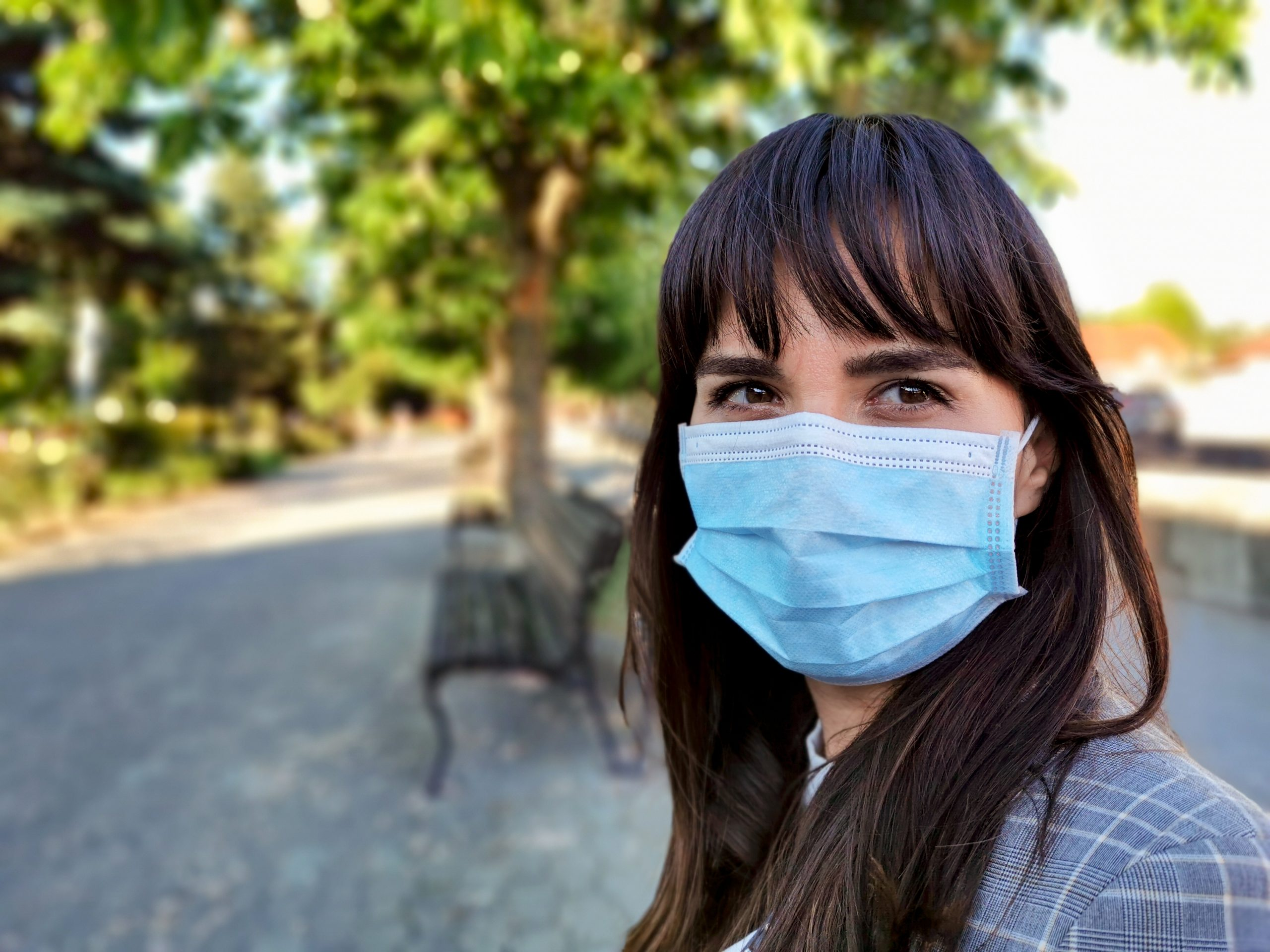 Young woman with bangs wearing a face mask in the city during COVID-19
