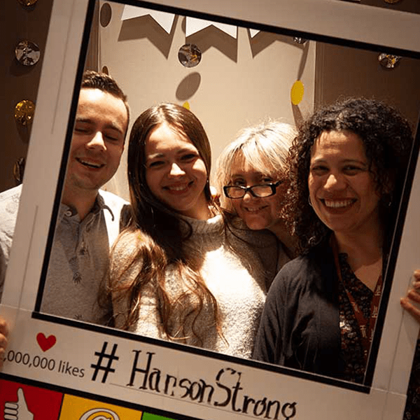 Hanson College staff members smiling in a photobooth frame