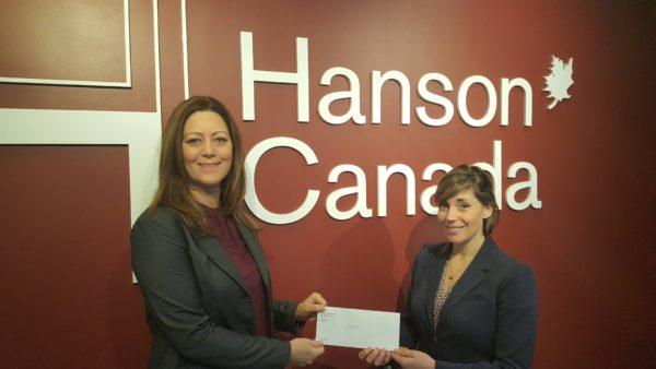 Two Caucasian females holding $1500 fundraising cheque at Hanson College