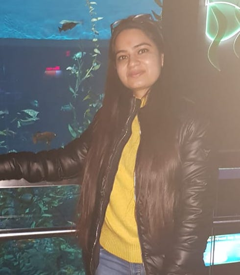 Selfie of an Indian female in a leather jacket over a yellow shirt at an aquarium