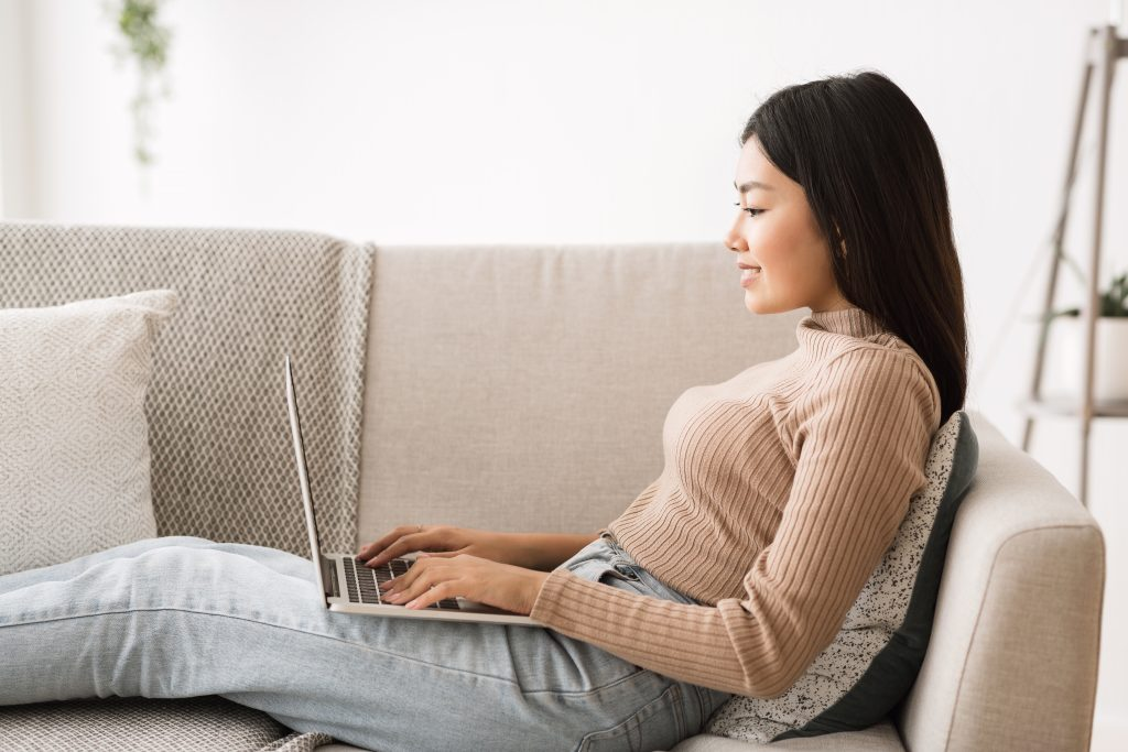 Asian freelancer girl working online on laptop, side view