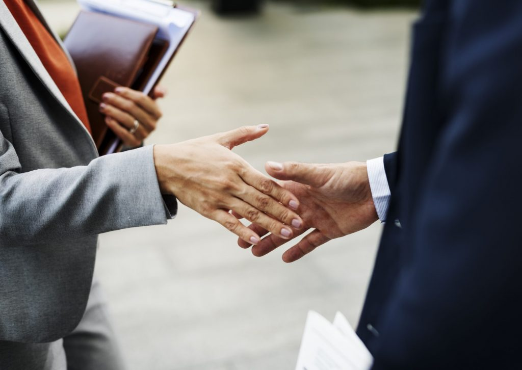 Corporate woman and man shaking hands in a partnership