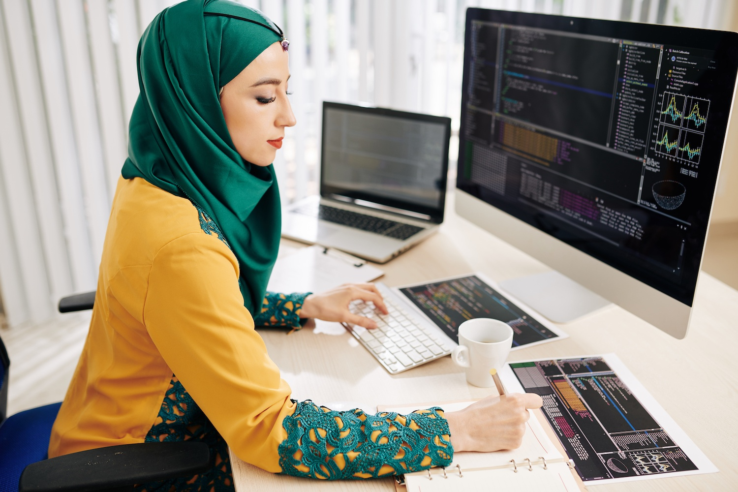 Young muslim female software developer working on programming code and taking notes in planner