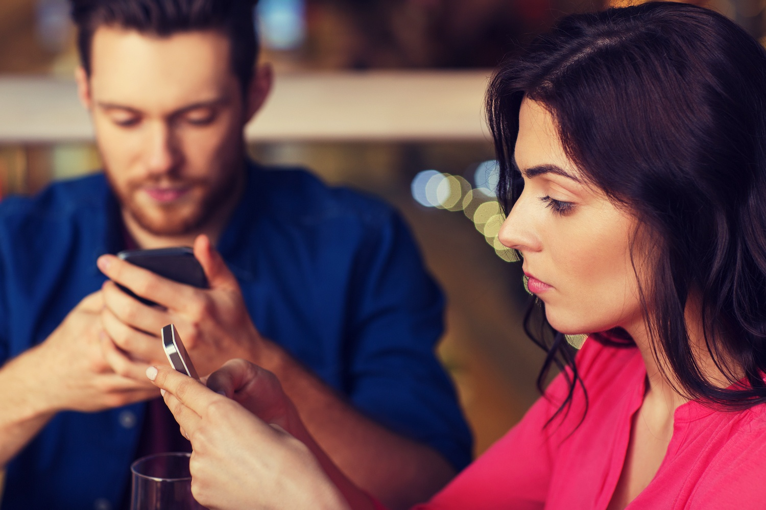 couple with smartphones dining at restaurant