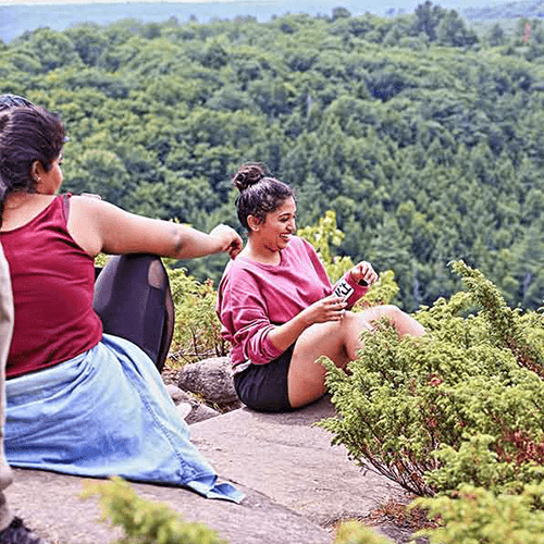 Two South Asian female students sitting on a hiking lookout and laughing